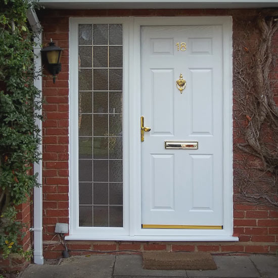 White six panel door with brassing fixtures and a block glass wall