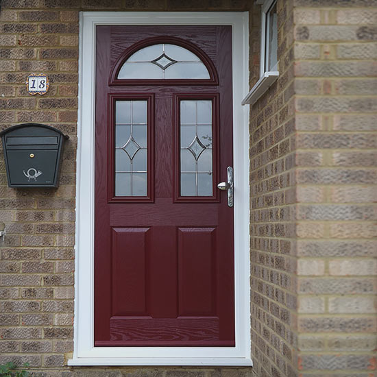 Rich red wooden door with three glass panels with diamond motif