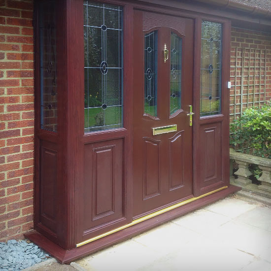 Brown Dark Wood cosmposite door in matching porch surround with lead linned effect on the glass