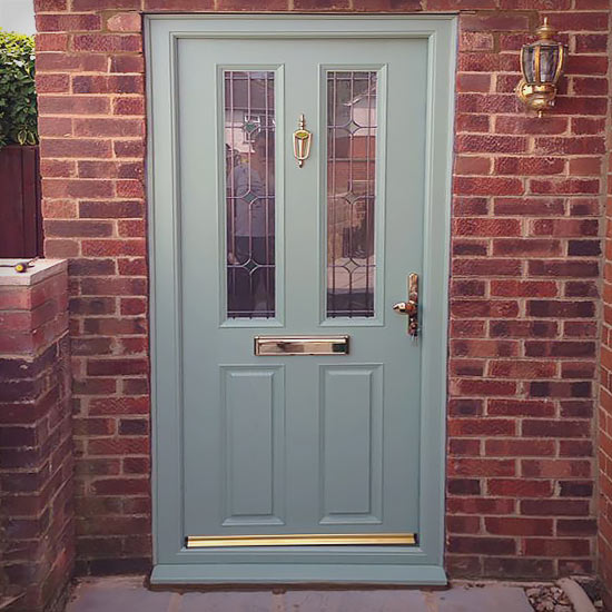 Pale green traditional door with brass fittings
