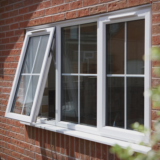 Finished installation of white triple glazed windows in a brick wall